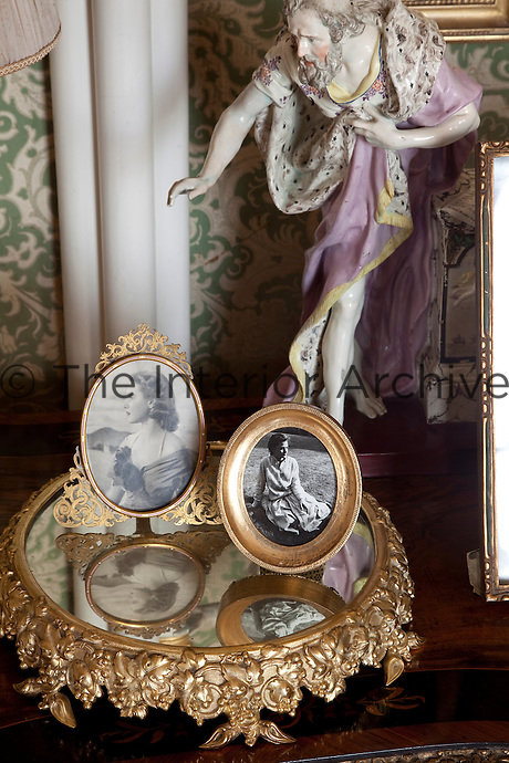 Two vintage photographs sit reflected in an ornate mirrored stand, overseen by a figurine