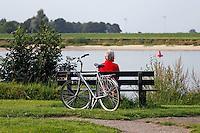 Man rust uit op een bankje aan de Lek