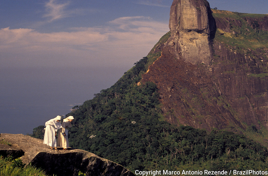 Nuns enjoying sightseeing in the mountains of Rio de Janeiro city, Brazil. Sister, sisters, member of a religious order, looking down, religion, Catholicism, Catholic, fun, recreation, amusement, diversion, entertainment.