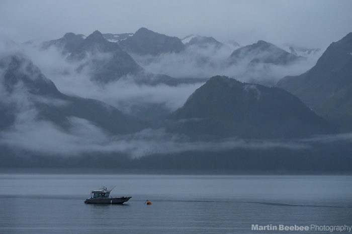 Fishing boat below misty mountains on Resurrection Bay, Seward, Alaska
