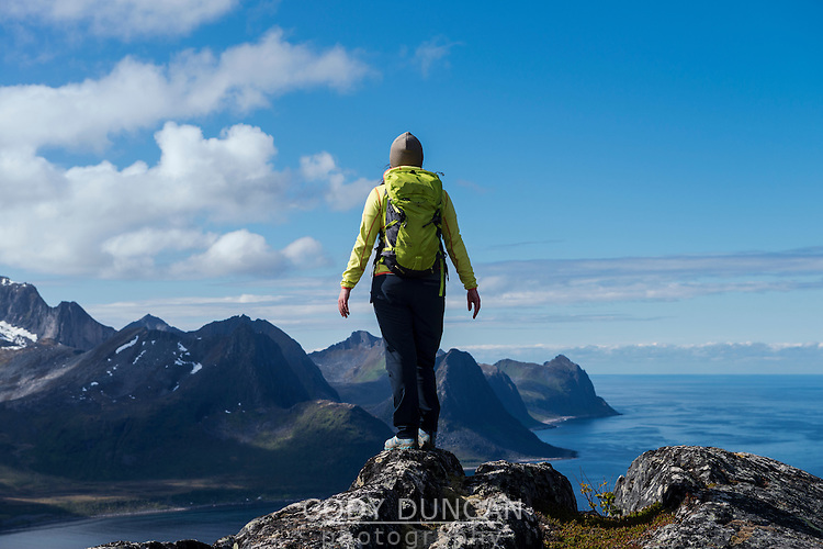 Female hiker on summit of Riven with Øyfjord in background, Senja, Troms, Norway