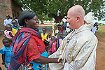 Father Tony O'Riordan, SJ, greets people after Catholic Mass in Bunj, the host community for the Doro Refugee Camp in Maban County, South Sudan. Doro is one of four camps in Maban that together shelter more than 130,000 refugees from the Blue Nile region of Sudan. Jesuit Refugee Service provides educational and psycho-social services to both refugees and the host community. Fr. O'Riordan directs the JRS work in Maban.<br /> <br /> Misean Cara supports the work of JRS in the Maban camps and host community.