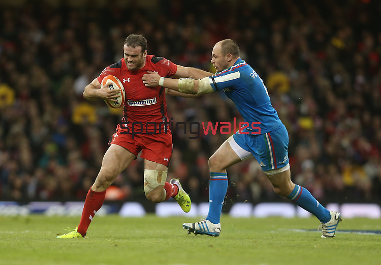 Wales centre Jamie Roberts tries to hand off Italian captain Sergio Parisse.<br /> RBS 6 Nations 2014<br /> Wales v Italy<br /> Millennium Stadium<br /> 01.02.14<br /> <br /> ©Steve Pope-SPORTINGWALES
