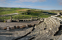High angle view of Theatre, c. 40-60 AD, Segobriga, Spain, pictured on April 13, 2006, in the afternoon showing the surrounding hills. Seating 2,000 people, the raked auditorium surrounds a semi-circular stage. The theatre was decorated with ornate columns and statues whose ruins remain. Segobriga was founded by the Romans in the 1st century BC, after the Punic wars, and the town was developed during the reign of  Augustus. It became an important administrative centre whose local industry was mining ëspecularis lapisí, a crystallized sheet gypsum used for window glass. Picture by Manuel Cohen.