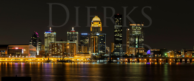 Louisiville, Kentucky city skyline illuminated at night with the Ohio River in the foreground.