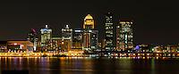 Louisiville, Kentucky city skyline illuminated at night with the Ohio River in the foreground.