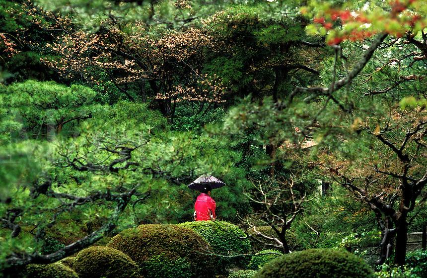 Japan. Kyoto. Geisha carrying a paper umbrella walks through the Heian Gardens