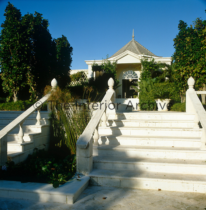 Coral stone steps lead up to the classical entrance of this Mustique beach house