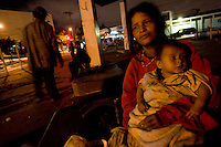 Sandra Guamux, 21, sits with her five-month-old son, Alfredo, at an abandoned gas station in Zone 4 of Guatemala City, Guatemala. About 20 otherwise homeless people live inside the station, and most are addicted to huffing paint thinner to numb the cold and their hunger pains. Guamux said a baby was stolen from her five days after it was born last year, and she is convinced the baby went into an illegal adoption system. She added that the police told her they would not investigate the situation since she had no photograph of the child.