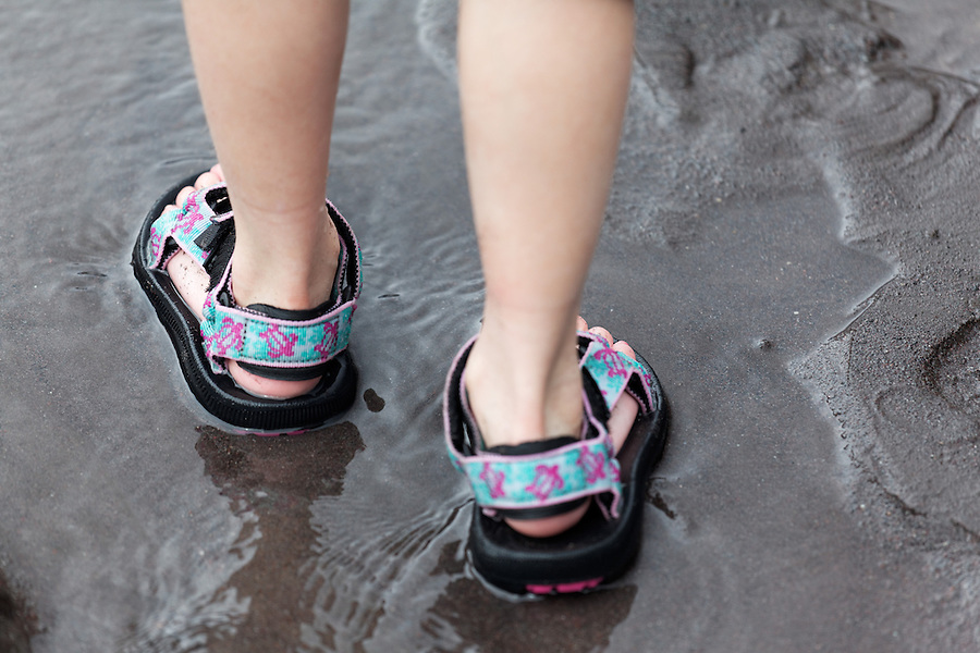 Feet of seven year old girl standing on wet sand, Nisqually River, Mount Rainier National Park, Washington, USA