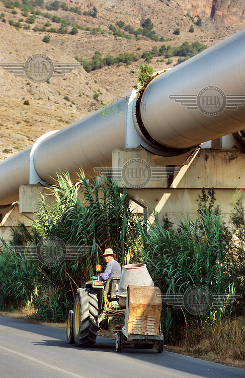 A construction worker drives a cement mixer beneath the huge pipes transporting water from the Tagus (Tajo) river to irrigate the surrounding land. In recent years there has been an explosion of controversial tourist-focused developments in Spain's arid southeastern region causing environmental degradation and placing enormous pressure on the limited water supplies in the area.