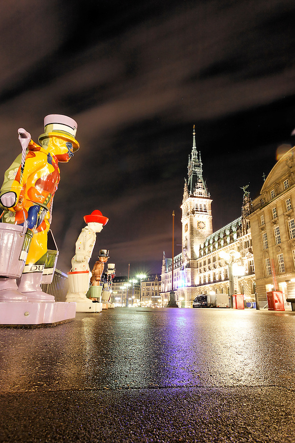 Statues of clowns carrying water overlook Rathausmarkt at night, Hamburg, Germany