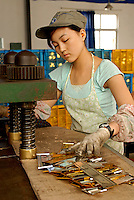 A female metal pressing machine operator on a busy production line at one of the worlds most successful brush manufacturers in the world. The Yixing Zhenxin Made Brush Co. Ltd produces a staggering 220,000 brushes every day using relatively non-high-tech but labour intensive methods for a variety of domestic and international clients. International clients include the home Depot, Wallmart and ICI to name a few..