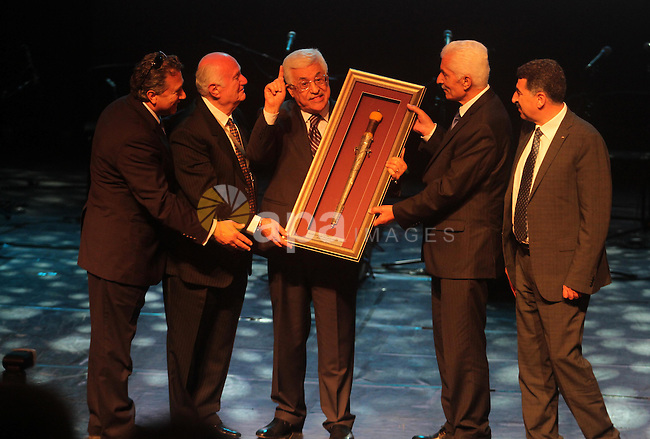 Palestinian President Mahmoud Abbas receives a gift during the 56th convention of the American Federation of Ramallah Palestine (ARFP), in the West Bank city of Ramallah on June 19, 2014 . Abbas condemned the abduction of three Israeli teens in the West Bank, saying the Palestinian Authority was searching for them and the perpetrators. Photo by Issam Rimawi
