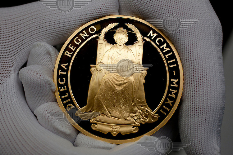 The Queen's Diamond Jubilee UK Five Ounce Gold Coin, freshly coined at the Royal Mint, near Llantrisant in Mid Glamorgan. As well as producing coinage for domestic use the mint also manufactures coins for around 60 countries worldwide.