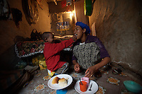 Tlbech, 27 years old, and her son Zarhiun, 4, both HIV positive share breakfast in their small house in one of the poorest neighborhoods in Addis Ababa, ethiopia on Friday July 28 2006..Talbech and Zarihun live on a 180 birr ( 20 USD ) per month sponsorship from the HfC NGO. they spend 100 Birr for rent leaving less than 10 USD for food and other necessities. Nevertheless they are a privileged family in the country..Tlbech besides fighting againt the virus and taking care of her child provides home base care assistance in Addis to other HIV patients in need..Ethiopia is one of the countries most affected by HIV/AIDS. Of its population of 77 million, three million are HIV-positive, according to government statistics. Every day sees 1,000 new infections. A million children under 14 have lost one or both parents to AIDS, and 200,000 children are living with AIDS. That makes Ethiopia the country with the most HIV-positive children.