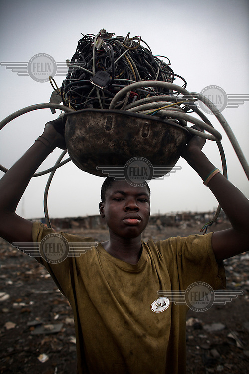 A boy carries electrical cables to a burning site at Agbogbloshie dump, which has become a dumping ground for computers and electronic waste from all over the developed world. Hundreds of tons of e-waste end up here every month. It is broken apart, and those components that can be sold on, are salvaged.
