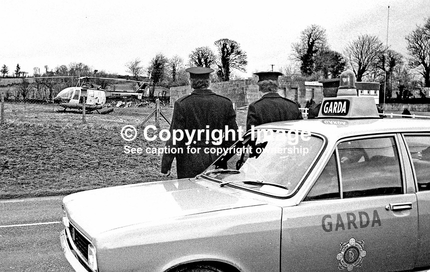 Garda officers stand guard at Cloughfin, Co Donegal, Rep of Ireland, where a helicopter was abandoned following a bombing attack on the RUC Station in Strabane, N Ireland, UK. The helicopter had been hijacked by a Provisional IRA team which included Eddie Gallagher and Rose Dugdale. The milk churn bombs dropped on the RUC station failed to detonate. 197401240042a.<br /> <br /> Copyright Image from Victor Patterson, 54 Dorchester Park, <br /> Belfast, UK, BT9 6RJ<br /> <br /> t1: +44 28 9066 1296 (from Rep of Ireland 048 9066 1296)<br /> t2: +44 28 9002 2446 (from Rep of Ireland 048 9002 2446)<br /> m: +44 7802 353836<br /> <br /> e1: victorpatterson@me.com<br /> e2: victorpatterson@gmail.com<br /> <br /> www.victorpatterson.com<br /> <br /> Please see my Terms and Conditions of Use at www.victorpatterson.com. It is IMPORTANT that you familiarise yourself with them.<br /> <br /> Images used on the Internet must be visibly watermarked i.e. &copy; Victor Patterson within the body of the image and copyright metadata must not be deleted. Images used on the Internet have a size restriction of 4kbs and will be chargeable at current NUJ rates unless advised otherwise.<br /> <br /> This image is only available for the use of the download recipient i.e. television station, newspaper, magazine, book publisher, etc, and must not be passed on to any third party. It is also downloaded on condition that each and every usage is notified within 7 days to victorpatterson@me.com<br /> <br /> The right of Victor Patterson to be identified as the author is asserted in accordance with The Copyright Designs And Patents Act (1988).