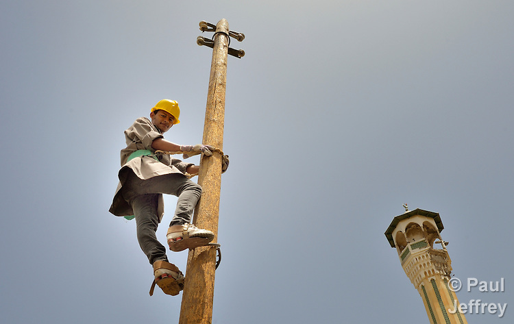 Student Emad Abu Holli climbs a utility pole during a class on electrical wiring at the Vocational Training Center in Khan Yunis, Gaza. The center is sponsored by the Department of Service for Palestinian Refugees of the Near East Council of Churches, and funded in part by the Pontifical Mission for Palestine. DSPR is a member of the ACT Alliance. A minaret is in the background.