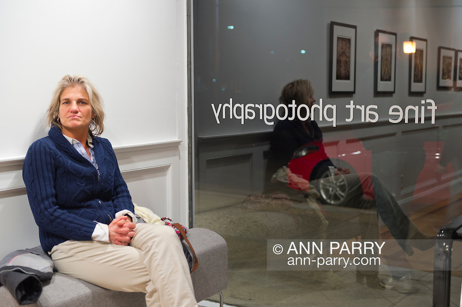 Huntington, New York, U.S. - March 1, 2014 - A visitor sits on a bench near the front window at the Opening Reception '3 Wild and Crazy Artists' at the FotoFoto Gallery.