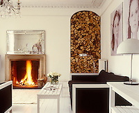 This black and white themed living room makes a feature of the store of logs which is piled floor to ceiling