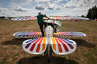 Man Getting Ready to Fly Multicolored White Biplane, Arlington Fly-In, WA, USA.