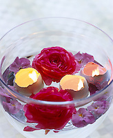 A clear glass bowl containing an Easter flower arrangement of flowers, eggshells and petals floating in water