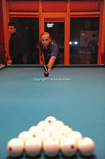 Ibrahim Ibrahimov plays billards after dinner in his home between Sangachal and Sahil, Azerbaijan on August 16, 2012.