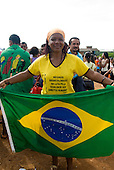 "Altamira, Brazil. ""Xingu Vivo Para Sempre"" protest meeting about the proposed Belo Monte hydroeletric dam and other dams on the Xingu river and its tributaries. Woman holding a Brazilian flag and wearing a t-shirt: ""blacks, whites, Indians in the fight for equality in human rights""."