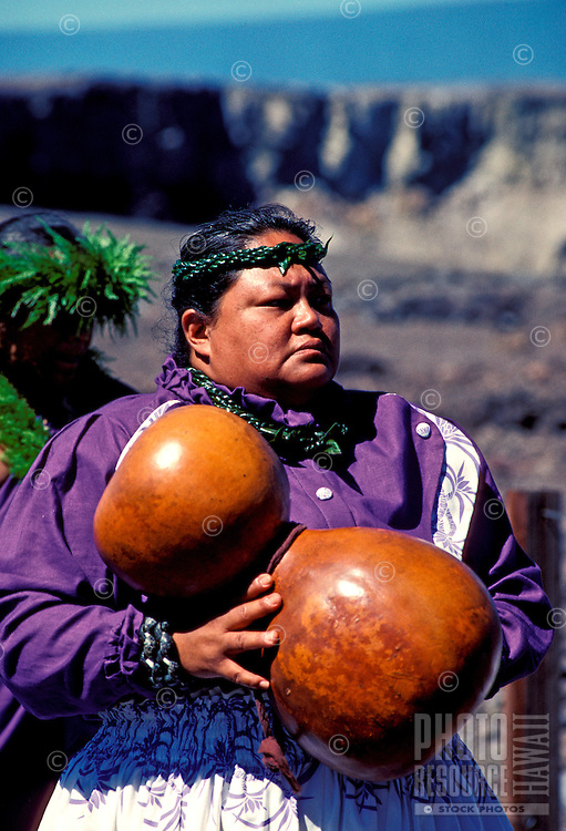 A native Hawaiian woman holds an ipu heke (gourd) which is tapped rhythmically to set the tempo or beat for hula dancers. Chants (oli) accompany this sacred art form.