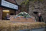 © Joel Goodman - 07973 332324 . 6 December 2013 . Marple , UK . Funeral Director Ian Mann (left) and Bob's son David Watson (right) tie Bob's coffin to the trailer . The funeral of farmer Bob Watson . His son David Watson drives his father's coffin on a trailer hooked to the back of Bob's favourite tractor through Marple via Bob's local pub before taking it on to the church . Photo credit : Joel Goodman