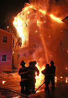 (01/08/2018- Lynn, MA) Firefighters battle the flames as a piece of roof collapses to the ground at the scene of a 4 alarm fire at an apartment building at 26 Broad Street in Lynn  on Monday, January 8, 2018. Staff Photo by Matt West