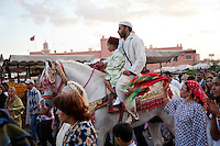 A father leads his son on a traditional procession through the Djemaa el Fna square in Marrakech, Morocco.