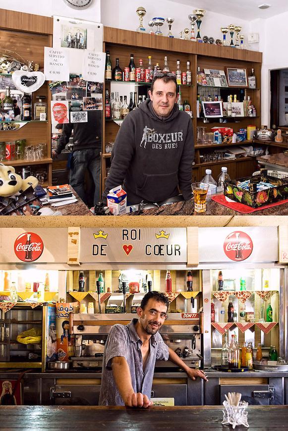 OPERE D'ARTE<br /> Luigi del B.A.R.L.U.I.G.I.<br /> Hocine Belhamri, barista<br /> <br /> Un bar di periferia<br /> con le foto e le coppe,<br /> clienti alla mattina <br /> un manipolo a pranzo<br /> pochi al pomeriggio.<br /> Impiegati, muratori, bottegai <br /> sempre gli stessi. <br /> Un posto qualunque di una citt&agrave;.<br /> Ma questo bar &egrave; diventato<br /> un&rsquo;opera d&rsquo;arte, <br /> un&rsquo;opera da prendere,<br /> una storia da raccontare. <br /> Un caff&egrave; un euro<br /> e l&rsquo;arte &egrave; gratis<br /> pronta da gustare.<br /> <br /> Il re di cuori sorride<br /> malizioso tra le ossa.<br /> Il braccio, le nocche in primo piano.<br /> Questo bar &egrave; un&rsquo;opera d&rsquo;arte,<br /> una storia lunga da raccontare.