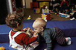 Berkeley CA Boy, age one, taking an oral interest in friend's book at day care  MR