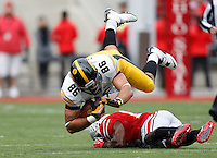 Ohio State Buckeyes cornerback Doran Grant (12) flips Iowa Hawkeyes tight end C.J. Fiedorowicz (86) in the first quarter of the NCAA football game between the Ohio State Buckeyes and the Iowa Hawkeyes at Ohio Stadium in Columbus, Saturday afternoon, October 19, 2013. The Ohio State Buckeyes defeated the Iowa Hawkeyes 34 - 24. (The Columbus Dispatch / Eamon Queeney)