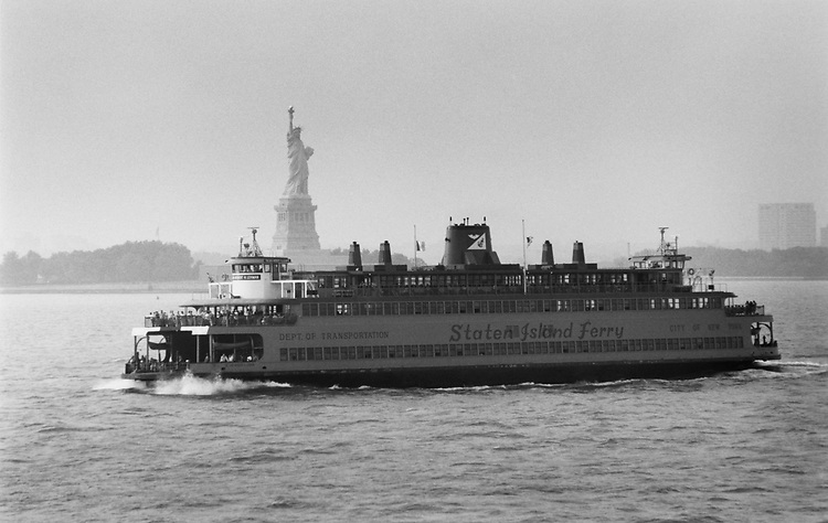 The Staten Island ferry passes in front of the Statue of liberty in August 1996. (Photo by Clifford Aversano/CQ Roll Call via Getty Images)