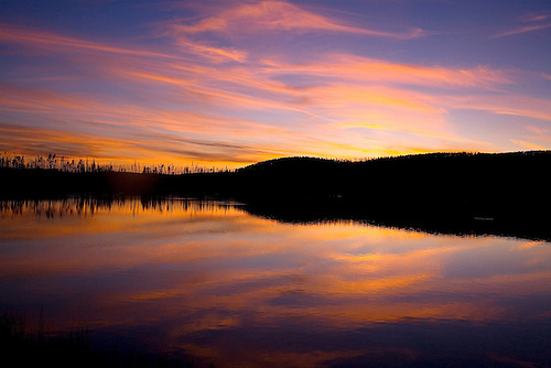 A SETTING SUN REFLECTS THE CLOUDS ABOVE ONTO GREBE LAKE IN YELLOWSTONE NATIONAL PARK,WYOMING