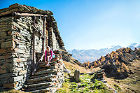 A female trail runner sits on the steps of a small house relaxing in the sun while running on the Maloja Pass to the Piz Lunghin, Switzerland.