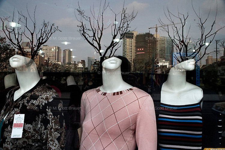 Leafless trees are visible in the reflection of a window in front  of mannequins displaying women's clothing in the Bund area of Shanghai, China.