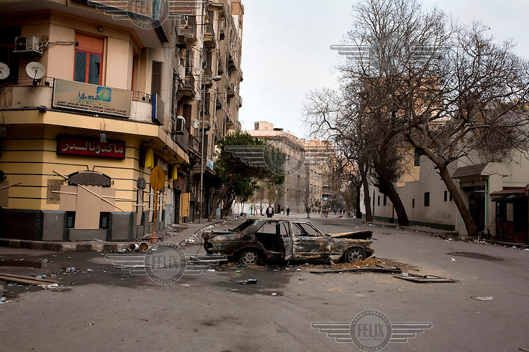A burnt out car on a street in central Cairo. Continued anti-government protests take place in Cairo calling for President Mubarak to stand down. After dissolving the government, Mubarak still refuses to step down from power.