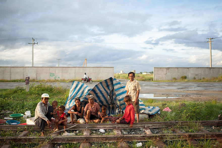 September 18, 2012 - Phnom Penh, Cambodia. A homeless family poses for a photograph in front of the tarp they live under near the lake that what once was Boeung Kak. © Nicolas Axelrod / Ruom