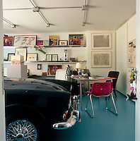 The garage doubles as a home office with a collection of drawings and paintings displayed on open shelving