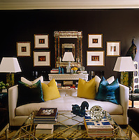 The console table to the rear of the cream sofa by Andrew Martin is flanked by Grecian prints and echoes the mantlepiece which stands on the opposite wall of the living room