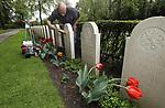 Foto: VidiPhoto<br /> <br /> RHENEN &ndash; Een slagveld op Ereveld De Grebbeberg in Rhenen maandag. De enorme hoosbuien van zondag op maandag hebben zeker de helft van de 10.000 uitbundig bloeiende tulpen verwoest. De bloemen hangen met hun kop naar beneden. Bovendien zit een groot deel van de grafstenen onder de modder. En dat terwijl de militaire begraafplaats er al perfect bij lag voor de herdenkingsplechtigheid van vrijdag 4 mei. Daarom wordt er de komende dagen door medewerkers van de Oorlogs Graven Stichting (OSG) met man en macht gewerkt om alles opnieuw strak en schoon te krijgen. De tulpen worden goeddeels vervangen door 300 vaasjes met 1500 snijtulpen. Die worden tussen de overgebleven bloemen geplaatst. De ruim 850 zerken worden met de hand schoongeborsteld, een enorme klus. Het is in mei 78 jaar geleden dat de Slag om de Grebbeberg plaatsvond.  Op het hoogtepunt van de slag, 12 mei 1940, stond er een overmacht van 23.000 Duitse militairen tegenover zo'n 2500 Nederlandse soldaten. Die laatsten hadden vrijwel geen munitie en voedsel, waren nauwelijks getraind en vochten bovendien met zwaar verouderde wapens. Opmerkelijk is dat het ereveld voor de Nederlandse militairen na de capitulatie door de Duitsers is aangelegd. Zij hielden er ook de eerste herdenking voor de gesneuvelde Nederlanders. De nationale herdenking op de Grebbeberg wordt vrijdag  4 mei bijgewoond door prinses Margriet en mr. Pieter van Vollenhoven. Sinds 1946 doet deze begraafplaats dienst als nationale herdenkingsplaats. Daarnaast vindt op Tweede Pinksterdag een herdenking plaats van het voormalig Achtste Regiment Infanterie, waar alle collega's die gesneuveld zijn tijdens de meidagen herdacht worden.