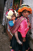 A woman carries her rather large, and slightly grubby, child on her back on market day in Ambato, which lies in Ecuador's Avenue of the Volcanoes.