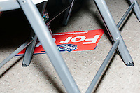 Campaign signs and stickers rest on the ground under chairs as Republican presidential candidate and Ohio governor John Kasich speaks at a town hall campaign event at the Derry VFW in Derry, New Hampshire.