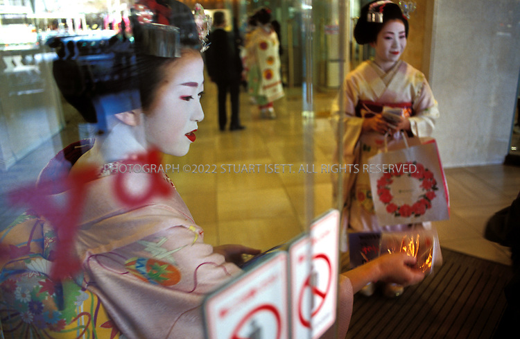 Kyoto, Japan..To earn extra cash, two young geisha hand out free tissues at a Kyoto department store. With business slow at traditional tea houses, geisha have been forced to seek other ways of making a living...All photographs ©2003 Stuart Isett.All rights reserved.