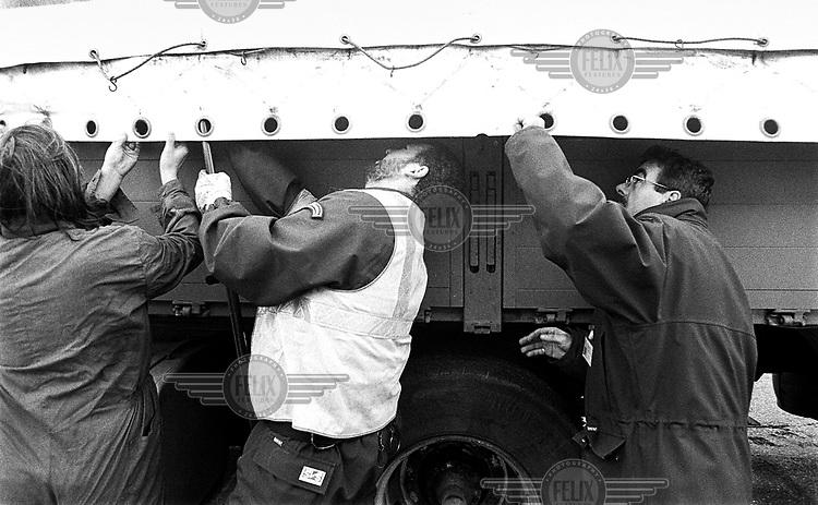 ©Piet den Blanken/Panos Pictures..France, Calais, november 2000.Illegalen proberen zich te verstopopen in vrachtwagens naar Engeland, Groot Brittannie, UK, te reizen..foto Piet den Blanken/Hollandse Hoogte.Frankrijk, Calais, november 2000.Bewaking van de haven van Calais. De bewaking controleert vrachtwagens op de aanwezigheid van illegalen tussen de lading. Aangetroffen illegalen worden overgedragen aan de politie. De controle gebeurt met CO2-meetapparatuur die uitgeademde lucht in de laadruimte meet..Illegalen worden gevonden tussen de lading van een vrachtwagen die zich inscheept op de veerpond naar Engeland. De bewakingsdienst van de haven draagt ze over aan de politie.