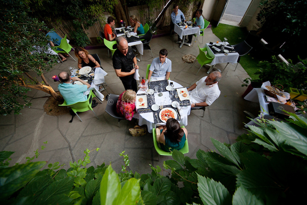 Diners in the shady garden of restaurant 'L'Atelier Gourmand', Montpellier, France, 14 July 2012